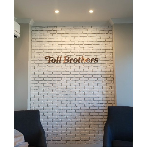Toll Brothers logo in a beautiful oil rubbed bronze dimensional lettering, mounted on brick.